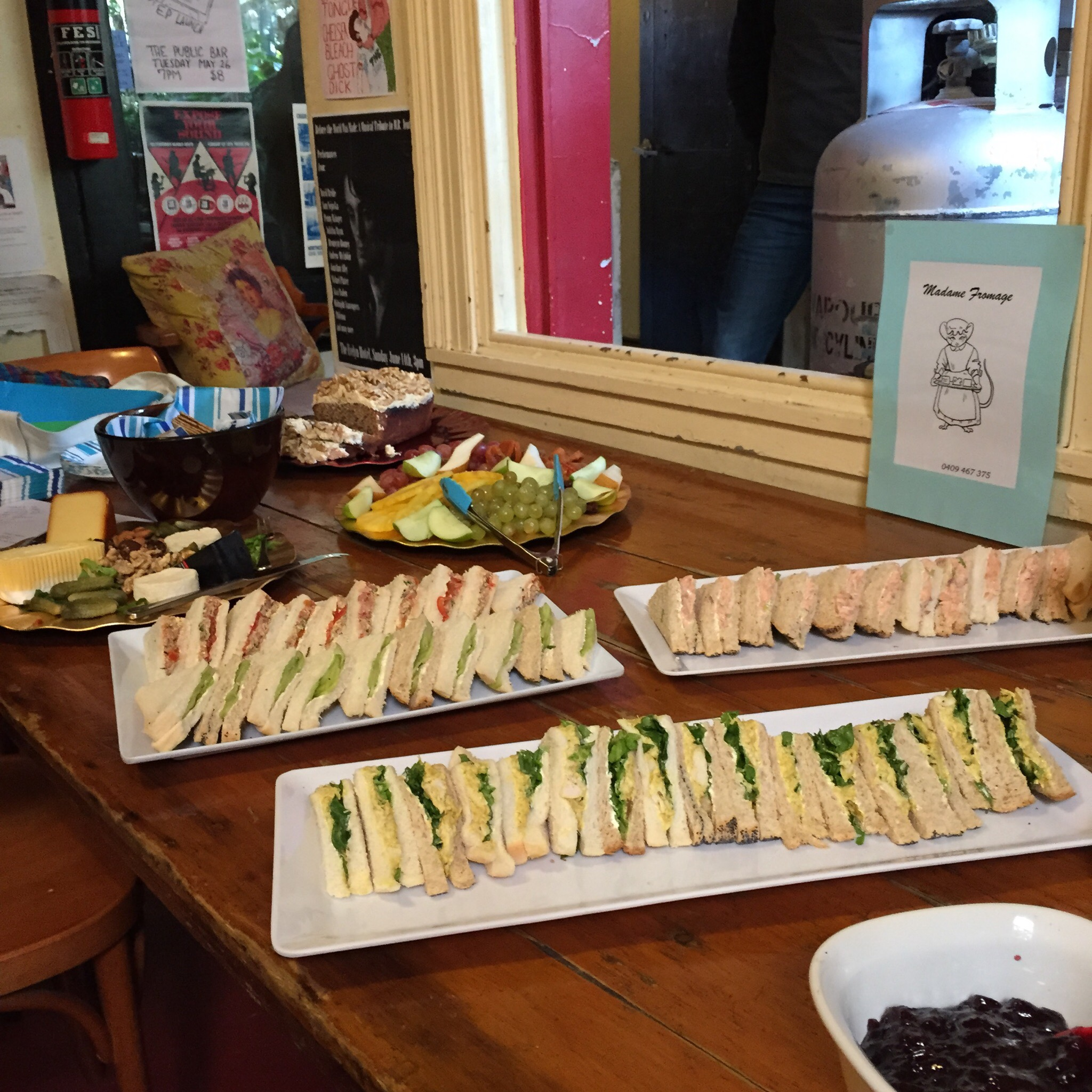 Plates of sandwiches, fruit, cheese and cake from Madame Fromage catering.